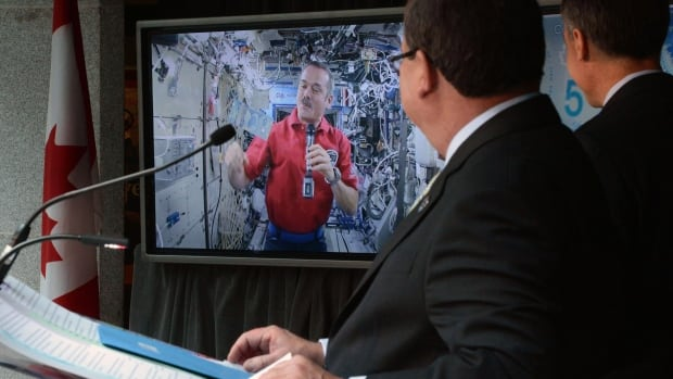 Astronaut Chris Hadfield unveils the new $5 bank note while aboard the International Space Station as then-finance minister Jim Flaherty and former Bank of Canada governor Mark Carney look on. New documents reveal Carney made the decision to beam Hadfield in live.