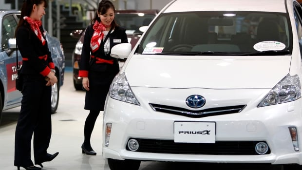 Showroom staff chat next to a Toyota Motor Corp Prius Alpha at its showroom in Tokyo February 4, 2014. Toyota Motor Corp raised its operating profit forecast for the financial year by 9 percent to a record 2.4 trillion yen ($23.7 billion) as the yen, which has fallen against the dollar by some 9 percent this financial year, buoys profits of the export-oriented car maker.