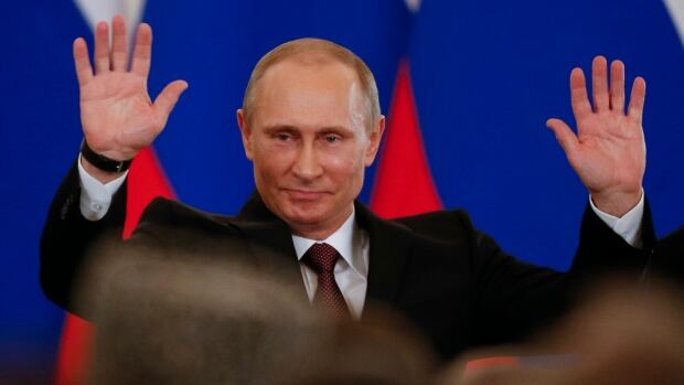 Russian President Vladimir Putin gestures after signing a treaty to incorporate Crimea into Russia in the Kremlin in Moscow, Tuesday, March 18, 2014.