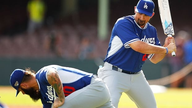 The Dodgers' Adrian Gonzalez, right, gestures towards his teammate Brian Wilson with a cricket bat during a workout at Sydney Cricket Ground on Wednesday. Things will be more businesslike on Saturday when Los Angeles opens the major league season in Australia  in the first of a two-game series against Arizona.