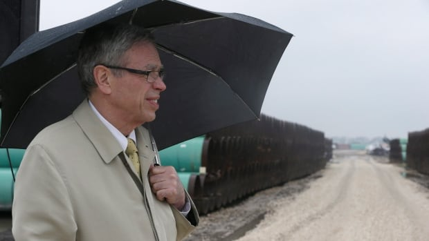 Canada's natural resources minister Joe Oliver stands in the rain after speaking at the TransCanada pipe yard for the Houston Lateral Project on March 5, 2014, in Mont Belvieu, Texas. The project will be a component of the Keystone Pipeline system.