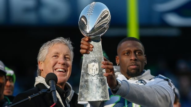 Seattle Seahawks coach Pete Carroll, left, and running back Jeremy Lane show off the Lombardi Trophy during ceremonies following the Super Bowl XLVIII Victory Parade on February 5. NFL owners will meet to discuss playoff expansion next week.