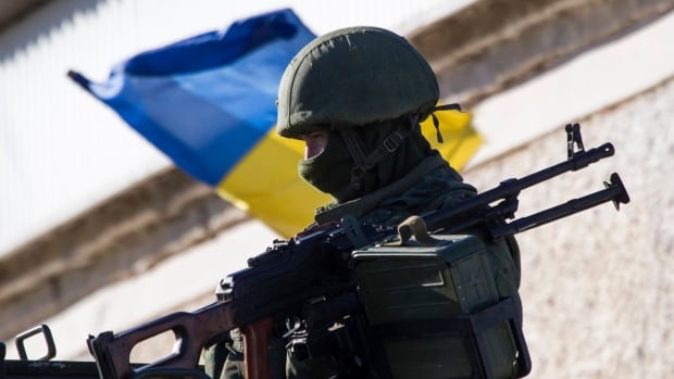 An armed man, believed to be a Russian serviceman, stands guard outside a Ukrainian military base in Perevalnoye, near the Crimean city of Simferopol, on Wednesday. Three Russian flags were flying at an entrance to Ukraine's naval headquarters in the Crimean port of Sevastopol on Wednesday, witnesses said, as pro-Russian forces took control of at least some of the base without armed resistance.