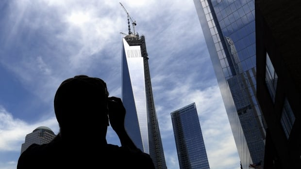 A teenage boy was arrested for breaking into the 1 World Trade Centre building in order to take pictures at night. Here, a pedestrian snaps a photo from ground level in Manhattan.