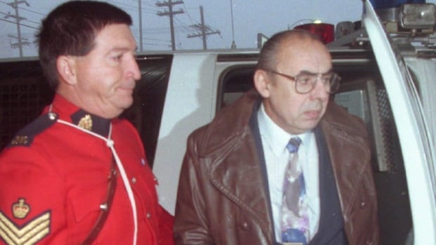 Roger Warren, right, is escorted from an RCMP van to the courthouse in Yellowknife in 1994. Warren, who was convicted of nine counts of second-degree murder in connection to the 1992 bombing at Yellowknife's Giant Mine, has applied for day parole.