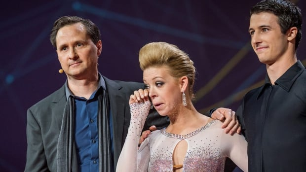 Dancer Adrianne Haslet-Davis, center, wipes away a tear while standing on stage with MIT professor Hugh Herr, left, and dancer Christian Lightner, at the 2014 TED Conference in Vancouver.