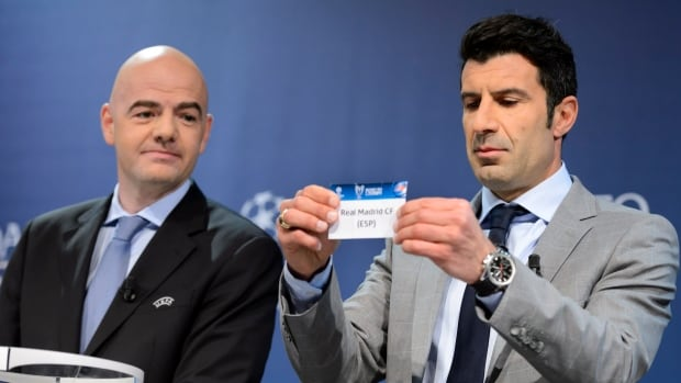 Former Portuguese  soccer player Luis Figo, right, shows a ticket with Spain's soccer team Real Madrid CF next to UEFA General Secretary Gianni Infantino, left, during the draw on Friday in Nyon, Switzerland.