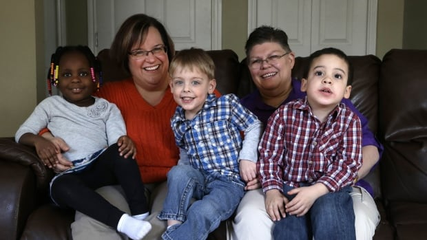 April DeBoer, second from left, sits with her adopted daughter Ryanne, 3, left, and Jayne Rowse, fourth from left, and her adopted sons Jacob, 3, middle, and Nolan, 4, right, at their home in Hazel Park, Mich.  The two nurses who've been partners for eight years claimed the ban on gay marriage violated their rights under the U.S. Constitution.