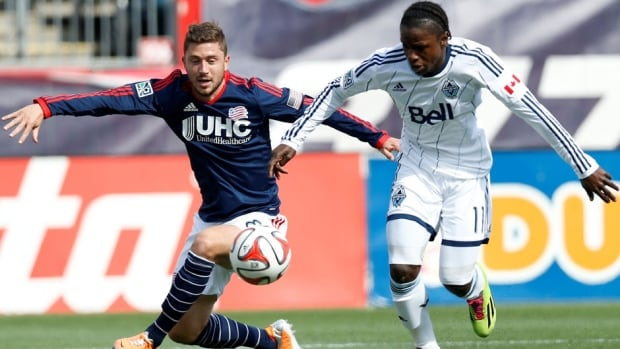 Vancouver Whitecaps forward Darren Mattocks (11) battles for the ball with New England Revolution defenceman Chris Tierney Saturday in Foxborough, Mass., Saturday.