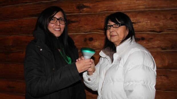 Karen Kejick hands a green light to an Anishinaabe woman from Onigaming First Nation at the 'Green Light Strategy' kick-off.