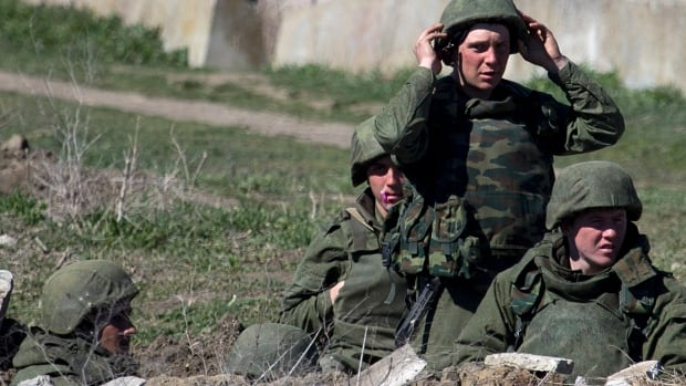 Pro-Russian soldiers in unmarked uniforms arrange a position near Ukrainian marines base in the city of Feodosia, Crimea, on Sunday. The Russian Defence Ministry said that as of Sunday the Russian flag was now flying over 189 military facilities in Crimea. It didn't specify whether any Ukrainian military operations there remained under Ukrainian control.