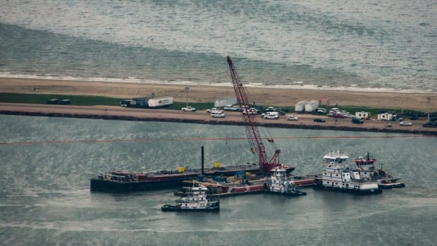 Emergency crews work along a barge that spilled oil after it was struck by a ship near the Texas City Dike on Sunday. Dozens of ships are in evolved in clean-up efforts after the oil spread 19 km out into the Gulf of Mexico.