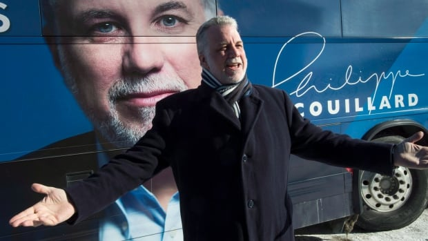 Liberal leader Philippe Couillard gestures in front of his campaign bus during a stop Monday, March 24, 2014 in Sherbrooke, Que. THE CANADIAN PRESS/Paul Chiasson