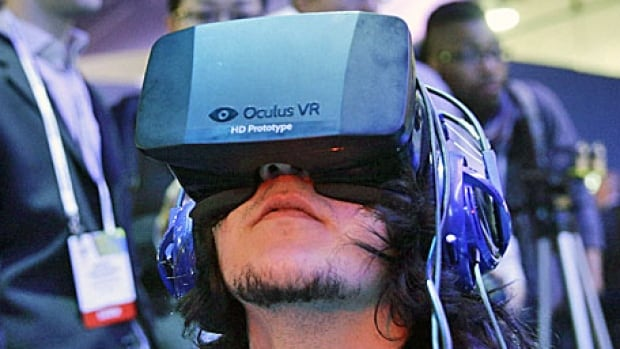 A man plays a video game wearing the Oculus Rift virtual reality headset at the 2014 International Consumer Electronics Show in Las Vegas. Facebook is buying Oculus for $2 billion.