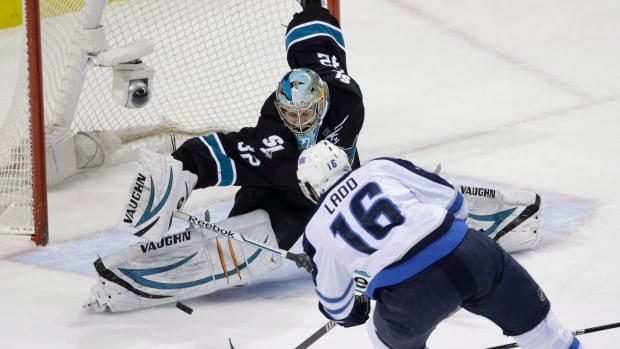 San Jose Sharks goalie Alex Stalock stops a shot by Winnipeg Jets' captain Andrew Ladd during a game in January. The captain returns to the team today after taking off the game against Dallas for his daughter's birth.