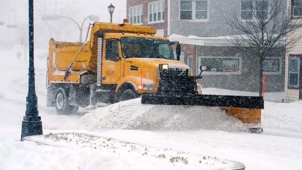 A snowplows clears streets in Dartmouth, N.S. on March 26. An early spring storm disrupted travel and closed schools and businesses across the region.
