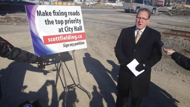 Scott Fielding stands near the intersection of Waverley Street and Taylor Avenue to announce his petition to get the city's roads repaired before extending rapid transit.