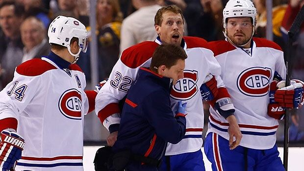 Montreal's Travis Moen, centre, had to be helped from the ice after being roughed up during a game in Boston this week.