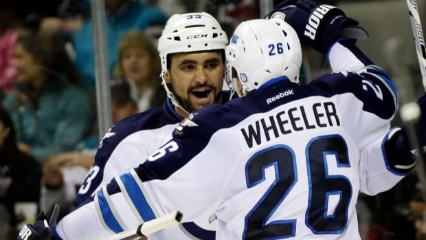 Jets' Dustin Byfuglien, left, celebrates his goal with Blake Wheeler during the second period of their game against the San Jose Sharks on Thursday. The Jets won 4-3 and Wheeler finished the game with a goal and two assists, include setting up the winner.
