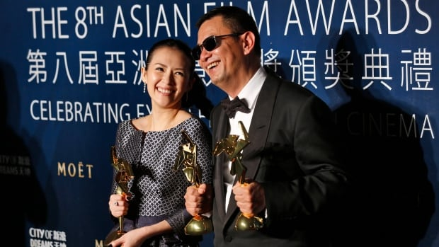 Director Wong Kar-wai and Chinese actress Zhang Ziyi pose with their trophies at the Asian Film Awards in Macau on Thursday.