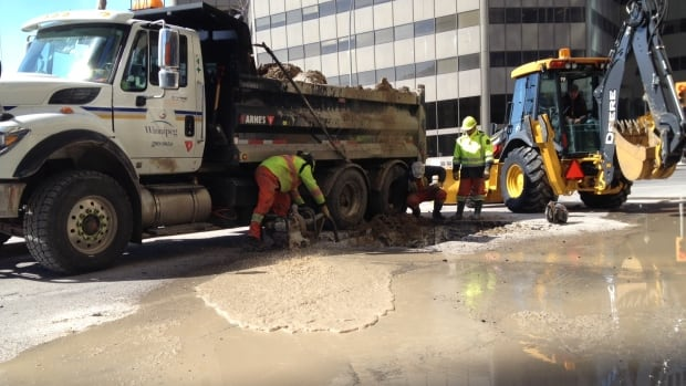 City of Winnipeg workers attend to a water main break at Main Street and Pioneer Avenue.
