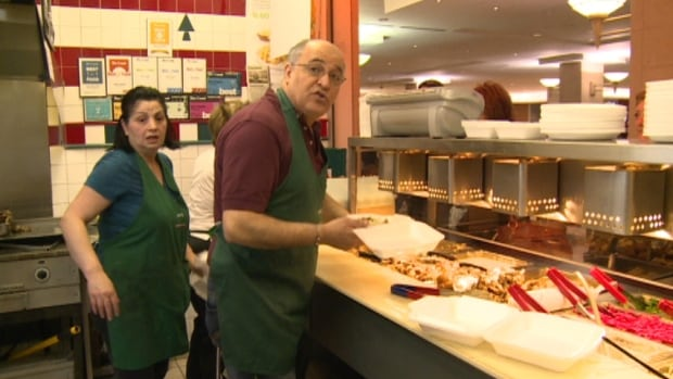 Raymond Khattar serves customers for the last time Friday before Ray's Lebanese Cuisine closes in the Scotia Square food court.