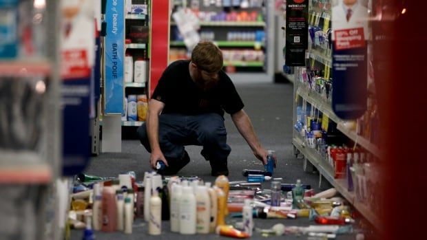 A man picks up fallen goods at a store in La Miranda, Calif., after a magnitude-5.1 earthquake was widely felt in the Los Angeles area and surrounding counties.