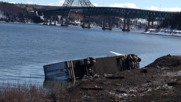 A tractor-trailer lies on its side after crashing near the Seal Island Bridge in Cape Breton.