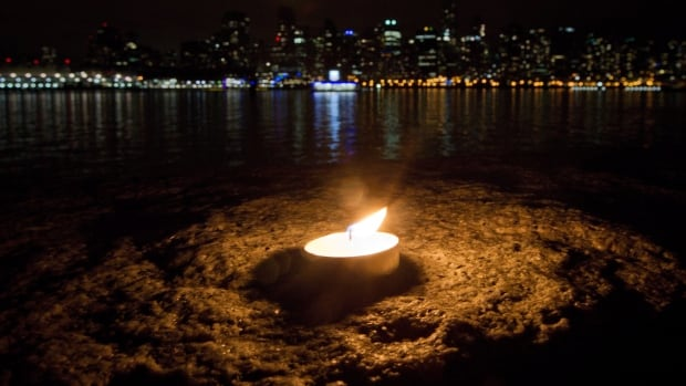 A candle burns on the Stanley Park seawall during Earth Hour in Vancouver, B.C., on Saturday March 31, 2012. People around the world are turn off their lights each year to reduce energy consumption and bring awareness to climate change.