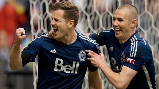 Vancouver Whitecaps' Jordan Harvey, left, and Kenny Miller, of Scotland, celebrate Harvey's goal against the Houston Dynamo during the first half in Vancouver, B.C., on Saturday.
