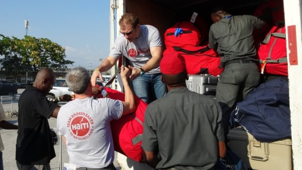 Apart from personnel, Team Broken Earth brings dozens of red duffle bags to Haiti loaded with medicine and medical supplies not easily found in the country. Team leader Dr. Andrew Furey helps locals load a truck at Port au Prince airport.