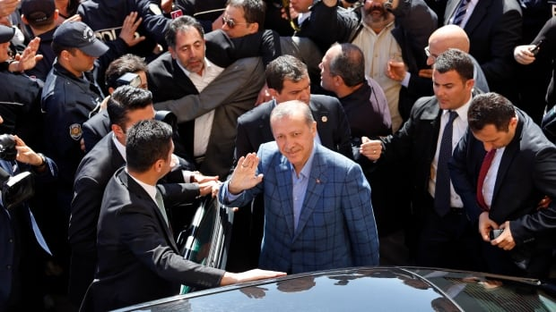 Turkey's Prime Minister Tayyip Erdogan waves to supporters during the municipal elections outside a polling station in Istanbul March 30, 2014. Erdogan looks set to win Sunday's municipal elections that have become a crisis referendum on his 10-year rule as he tries to ward off graft allegations and stem a stream of damaging security leaks.