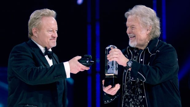 Randy Bachman holds the Juno as Robbie Bachman videotapes a closeup of the trophy after being inducted into the Canadian Music Hall of Fame at the Juno Awards in Winnipeg, Sunday, March 30.