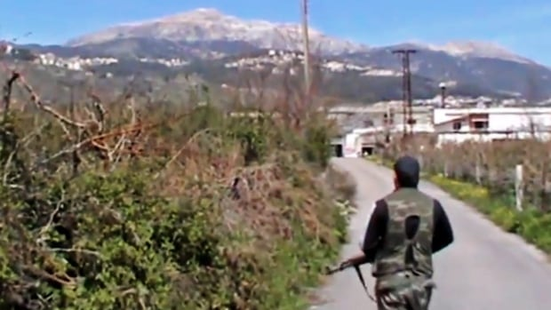 This Sunday, March 23, 2014 image taken from video obtained by the anti-government activist group Shaam News Network, which has been authenticated based on its contents and other AP reporting, shows a Syrian fighter holding his weapon after seizing the predominantly Armenian Christian town of Kessab, Syria. The rebels, including militants from the al-Qaeda-affiliated Nusra Front, have also wrested control of a nearby border crossing to Turkey.