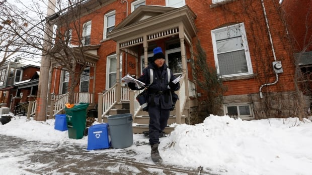 A Canada Post employee delivers mail in Ottawa. Canada Post is hiking the cost of postage stamps to try to stem soaring losses.