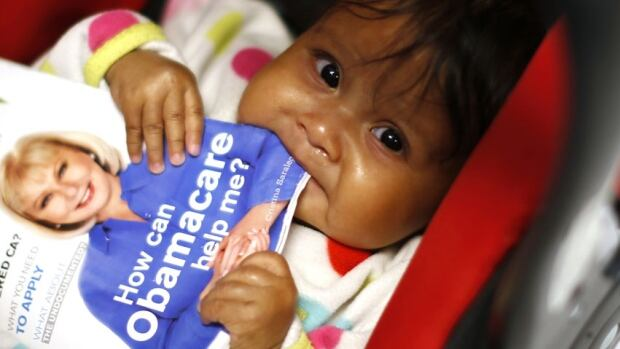 Six-month-old Hazel Garcia chews a pamphlet at a health insurance enrolment event California. A surge in enrolment numbers before the March 31st sign-up deadline was complicated by a technical glitch on the government's health insurance website.