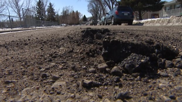 Water gets into the road and freezes, causing potholes.
