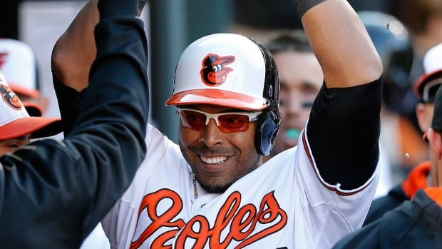 Nelson Cruz high-fives his Orioles teammates in the dugout after hitting a solo home run in the seventh inning. Baltimore went on to win 2-1 over the Boston Red Sox.