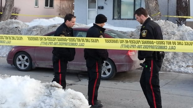 Winnipeg police officers outside a house in the 500 block of Seven Oaks Avenue where shots were fired early Tuesday.  The same house was targeted on Monday.