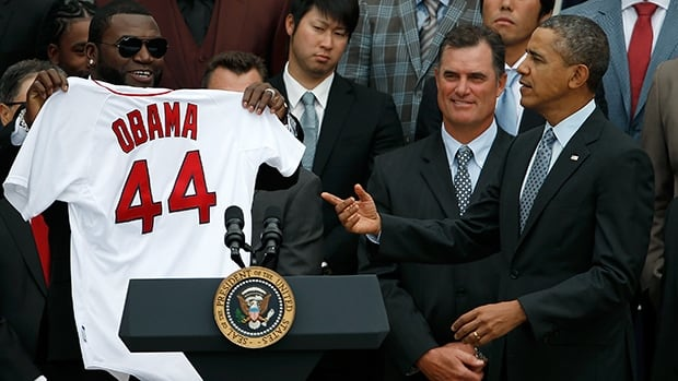 Boston Red Sox designated hitter David Ortiz, left, holds a Red Sox jersey presented to U.S. President Barack Obama on Tuesday in Washington, DC.