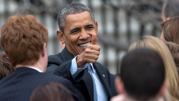 U.S. President Barack Obama gives the thumbs up during a ceremony on the south lawn of the White House in Washington, Tuesday, April 1, 2014, to honour the 2013 World Series baseball champion Boston Red Sox. The White House was also in a celebratory mood Tuesday because of its announcement that more than seven million people signed up for a health insurance plan by Monday's deadline.