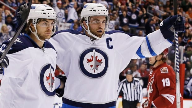 The Jets' Andrew Ladd, right, celebrates a goal with Michael Frolik last season.