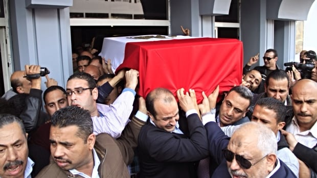 Mourners for Egyptian police Gen. Tarek el-Mergawy carry his coffin during his funeral at the police hospital in Aguza neighborhood of Giza, Egypt, Wednesday. The bombs exploded earlier outside Cairo University's main campus, hitting riot police deployed against near daily protests by Islamist students.