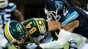 Marcus Ball, right, grabs a hold of Edmonton's Kyle Norris during an August 2013 CFL game in Toronto.