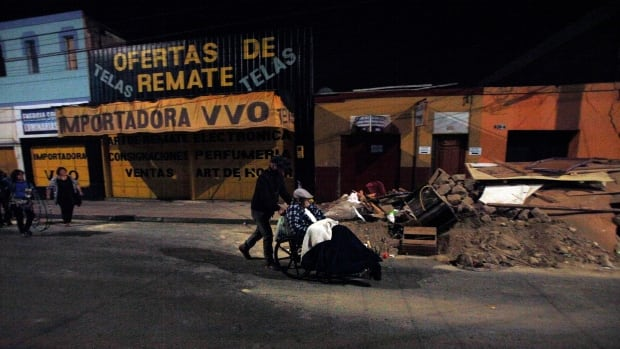 A man is pushed in a wheelchair to a safety area after a strong aftershock in Arica, Chile, early Thursday.