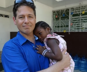 Anthony Germain with orphaned girl in Port-au-Prince