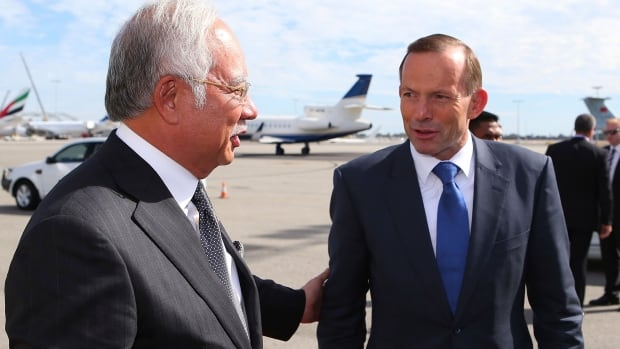 Australian Prime Minister Tony Abbott, right, chats with his Malaysian counterpart Najib Razak at Perth International Airport as Razak prepares to depart Australia after his visit during the search of the missing Malaysia Airlines flight MH370, in Perth on Thursday. Najib met with Abbott and got a briefing by Angus Houston, the head of a joint agency co-ordinating the search.