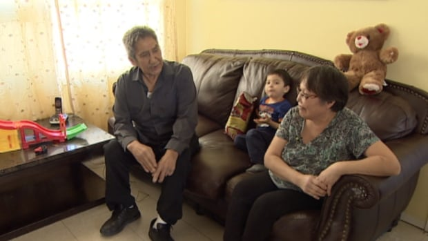Harvey and Sheila Field sit with their two-year-old grandson Jayden. The couple have used money from the residential school settlement to keep up with the costs of raising four grandchildren. Now they're appealing to their band and the government to help keep the kids out of foster care.