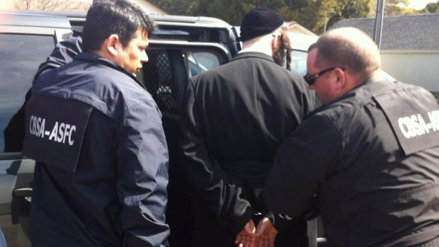 Canada Border Services Agency agents take a member of the ultra-orthodox Jewish sect Lev Tahor into custody in Chatham, Ont., on Wednesday, April 2, 2014.
