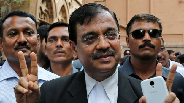 Public prosecutor Ujjwal Nikam displays the victory symbol as he comes out of a court in Mumbai Friday, after the court sentenced to death three men who raped a photojournalist last year.
